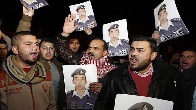 Relatives of Islamic State captive Jordanian pilot Muath al-Kasaesbeh hold up his pictures as they chant slogans during a demonstration in Amman