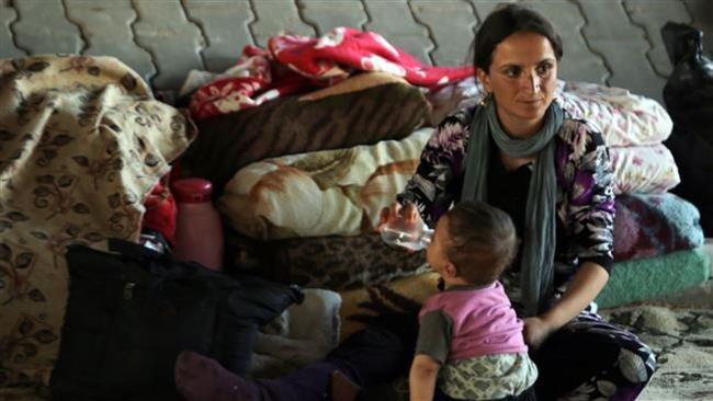 Egy iraki izadi nő egy gyermek mellett ül egy híd alatt, mert ott talált menedéket, miután az ISIL fegyveresek megtámadták Sinjar várost 2014. augusztus 17-én.
