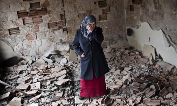 Egy nő áll egy a május 08-09-ei kumanovoi harcban szétlőtt házban
