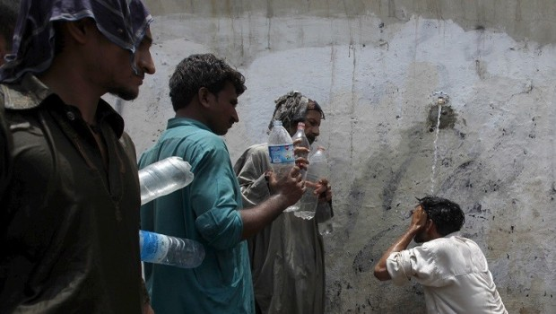 A man cools off under a public tap, while others wait to fill their bottles, during intense hot weather in Karachi
