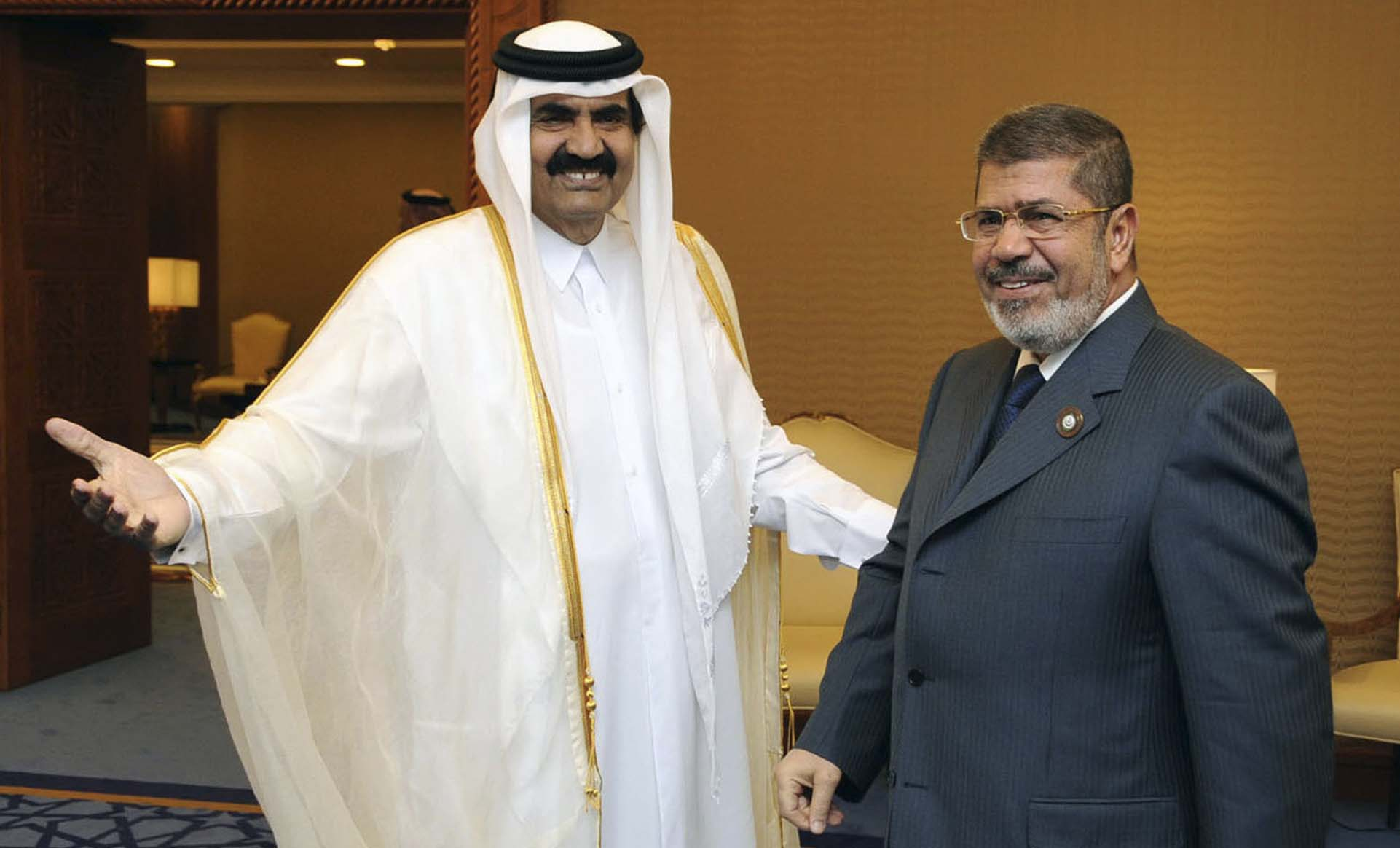 Qatar's Emir Sheikh Hamad bin Khalifa al-Thani greets Egypt's President Mohamed Mursi during the Arab League summit in Doha