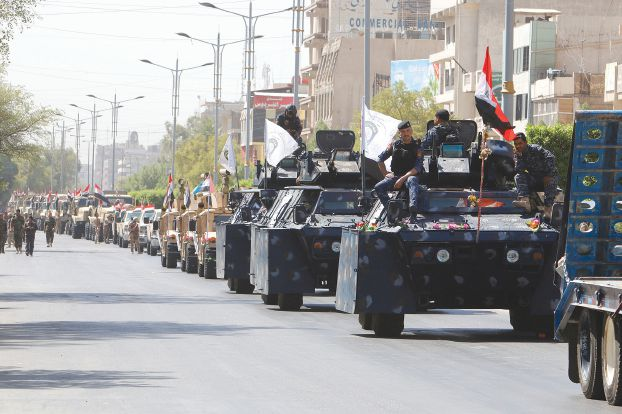 Iraqi security forces vehicles take part in a military parade in the streets of Baghdad