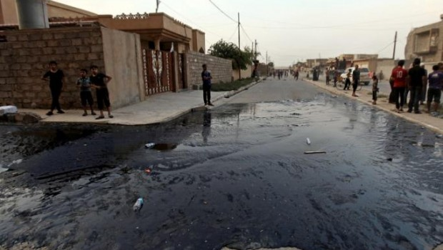 Residents look at oil spill from wells in Qayyara
