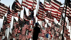 Visitors walk amongst US national flags erected by students and staff from Pepperdine University as they pay their respects to honor the victims of the September 11, 2001 attacks in New York, at their campus in Malibu, California on September 10, 2016.  The students placed aound 3,000 flags in the ground in tribute to the nearly 3,000 victims lost in the attacks almost 15 years ago.  / AFP PHOTO / Mark RALSTON
