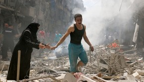 TOPSHOT - People walk amid the rubble of destroyed buildings following a reported air strike on the rebel-held neighbourhood of al-Kalasa in the northern Syrian city of Aleppo, on April 28, 2016. The death toll from an upsurge of fighting in Syria's second city Aleppo rose despite a plea by the UN envoy for the warring sides to respect a February ceasefire. / AFP PHOTO / AMEER ALHALBI