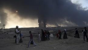 Moszul, 2016. október 19. Sűrű füst borítja be az eget, amint az otthonukat elhagyott moszuli lakosok gyalogolnak el az iraki biztonsági erők tagja mellett az észak-iraki nagyáros határában 2016. október 18-án. Az előző nap az iraki kormányhadsereg és az iraki kurd erők, a pesmergák az Egyesült Államok vezette koalíció légi és szárazföldi támogatásával nagyszabású hadműveletet kezdett Moszul visszafoglalására az Iszlám Állam dzsihadista szervezet fegyvereseitől. (MTI/AP)