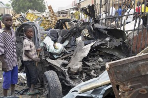 Two boys stand near the charred chassis of a vehicle after a bomb attack near a busy market area in Ajilari-Gomari near the city's airport, in Maiduguri March 2, 2014. REUTERS/Stringer