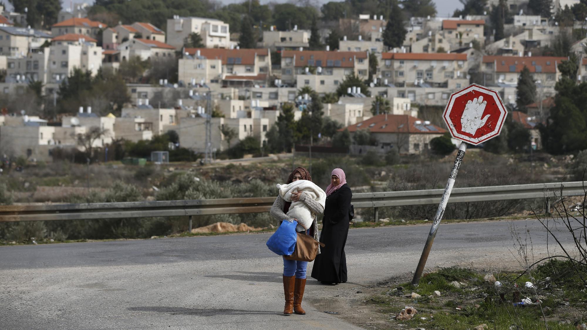 Palesztin asszonyok a Jalazoun menekülttáborból egy rámalláhi útkereszteződésben, mögöttük a Beit El seen zsidó telep Fotó: Abbas Momani / AFP