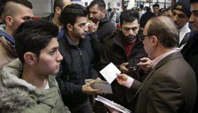 Hazájukba visszatérő iraki férfiaknak úti okmányokat osztanak a német rendőrség irodája előtt a berlini Tegel nemzetközi repülőtéren 2016. február 3-án. (MTI/AP/Michael Sohn)